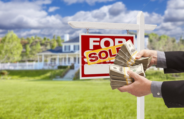Man Handing Over Money in Front Sold House and Sign Stock photo © feverpitch