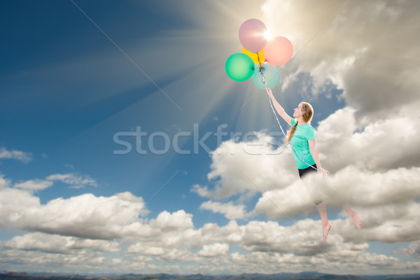 Young Adult Female Being Carried Up and Away Into The Clouds By  Stock photo © feverpitch