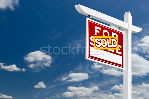Left Facing Sold For Sale Real Estate Sign Over Blue Sky and Clo Stock photo © feverpitch