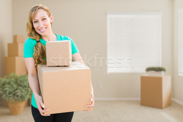Happy Young Adult Woman Holding Moving Boxes In Empty Room In A  Stock photo © feverpitch