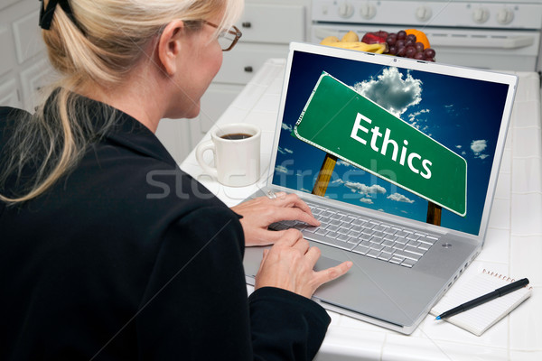 Woman In Kitchen Using Laptop with Ethics Sign Stock photo © feverpitch
