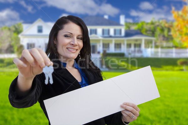 Woman Holding Blank Sign and Keys In Front of House Stock photo © feverpitch