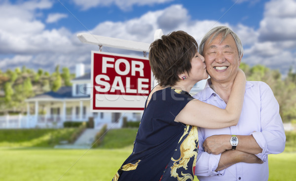 Affectionate Senior Chinese Couple In Front of House and Sign Stock photo © feverpitch