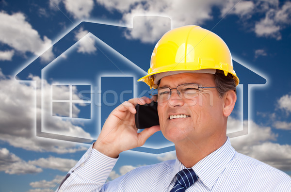 Contractor in Hardhat on Phone Over House Icon and Blurry Clouds Stock photo © feverpitch