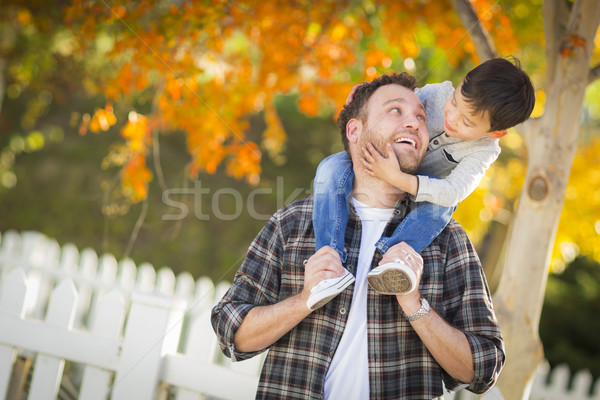 Mixed Race Boy Riding Piggyback on Shoulders of Caucasian Father Stock photo © feverpitch