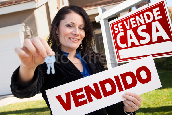 Hispanic Woman Holding Vendido Sign in Front of Se Vende Casa Si Stock photo © feverpitch