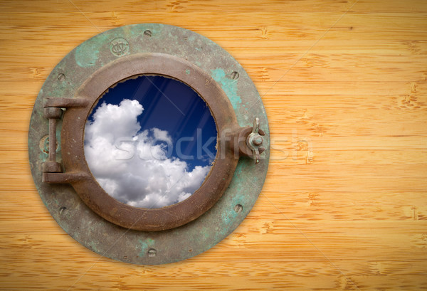 Antique Porthole on Bamboo Wall with View of Blue Sky and Clouds Stock photo © feverpitch