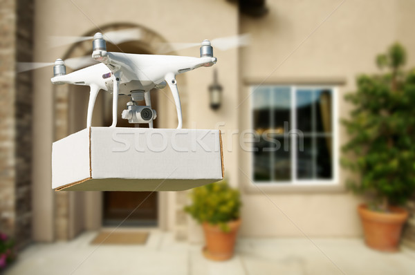 Stock photo: Unmanned Aircraft System (UAV) Quadcopter Drone Delivering Packa