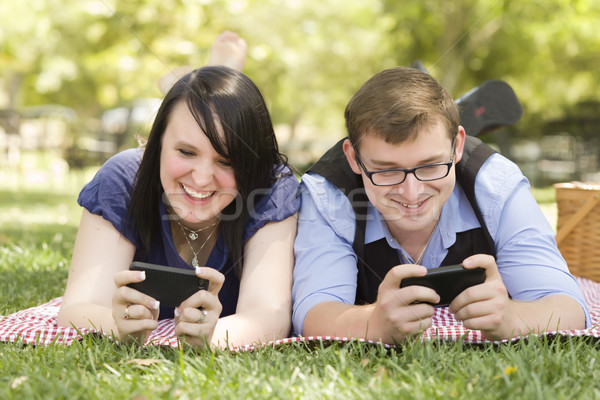 Young Couple at Park Texting Together Stock photo © feverpitch