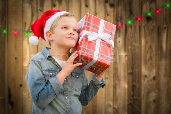 Curious Boy Wearing Santa Hat Holding Christmas Gift On Wood Stock photo © feverpitch