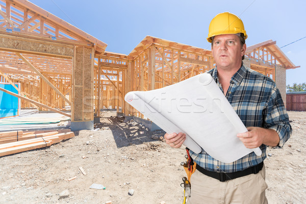 Male Contractor With House Plans Wearing Hard Hat In Front of Ne Stock photo © feverpitch