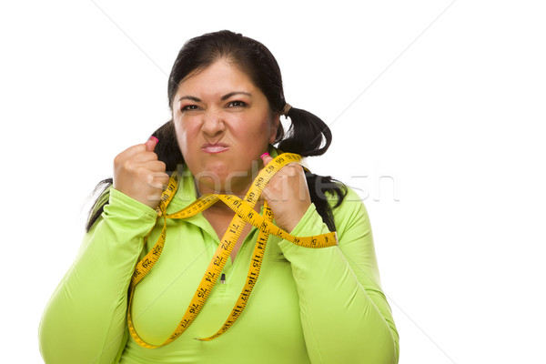 Frustrated Hispanic Woman Tied Up With Tape Measure Stock photo © feverpitch