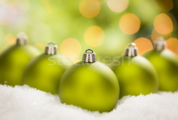Green Christmas Ornaments on Snow Over an Abstract Background Stock photo © feverpitch