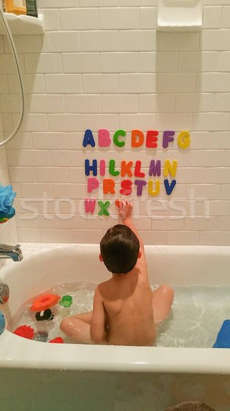 Young Boy Having Fun With The Alphabet On Wall At Bath Time Stock photo © feverpitch