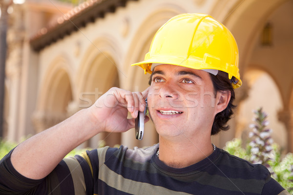 Handsome Hispanic Contractor on Phone with Hard Hat Outside Stock photo © feverpitch