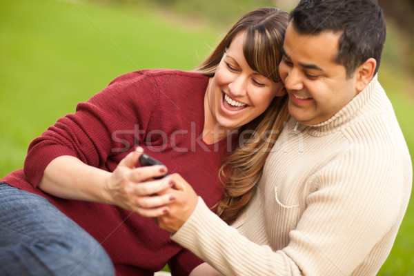 Attractive Mixed Race Couple Enjoying Their Camera Phone Stock photo © feverpitch