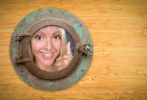 Antique Porthole on Bamboo Wall, Woman with Thumbs Up Looking Stock photo © feverpitch