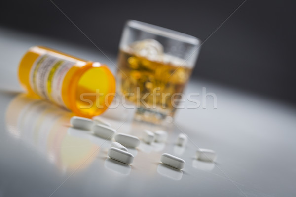 Prescription Drugs Spilled From Fallen Bottle Near Glass of Alco Stock photo © feverpitch