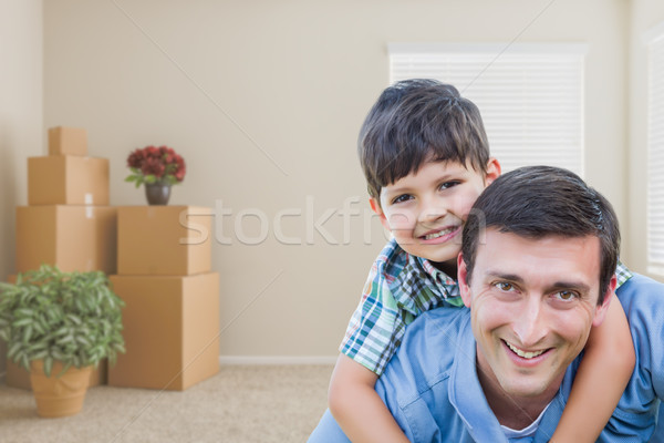 Father and Son in Room with Packed Moving Boxes and Potted Plant Stock photo © feverpitch