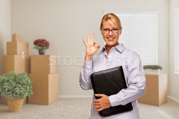 Woman with Okay Sign in Empty Room with Packed Moving Boxes Stock photo © feverpitch