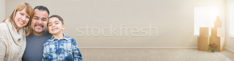 Mixed Race Family In Empty Room With Moving Boxes Banner. Stock photo © feverpitch