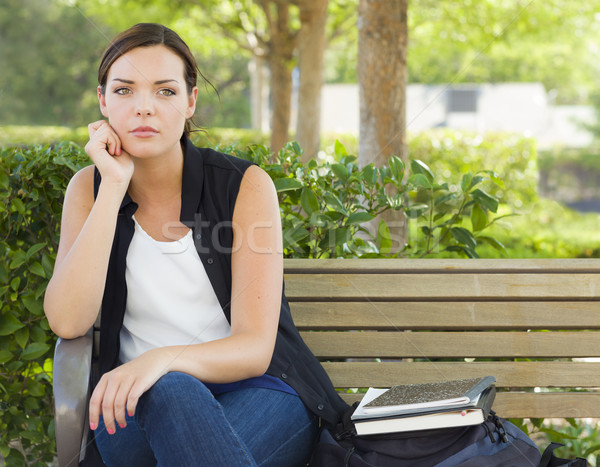 Stock photo: Melancholy Young Adult Woman Sitting on Bench Next to Books