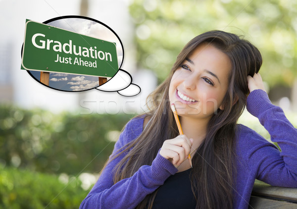 Stock photo: Young Woman with Thought Bubble of Graduation Green Road Sign