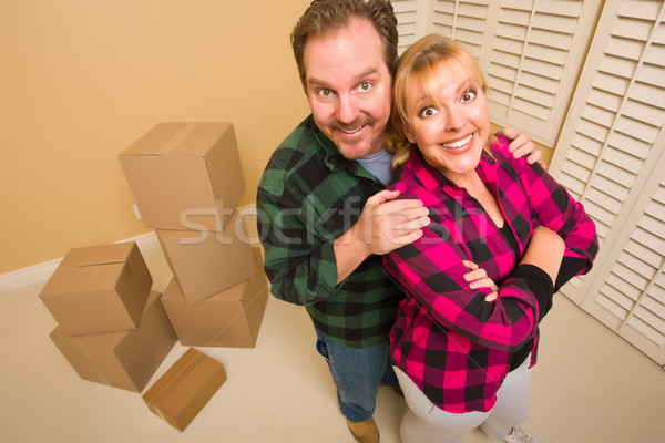 Proud Goofy Couple and Moving Boxes in Empty Room Stock photo © feverpitch