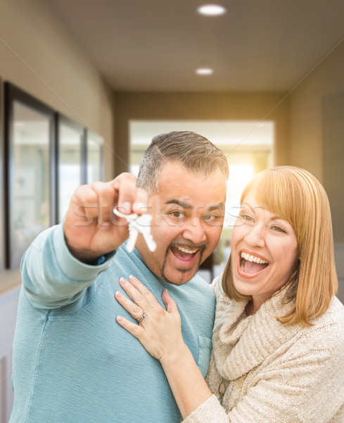 Couple Holding House Keys Inside Hallway of Their New Home Stock photo © feverpitch