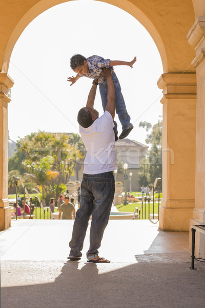 African American Father Lifting Mixed Race Son in the Park Stock photo © feverpitch