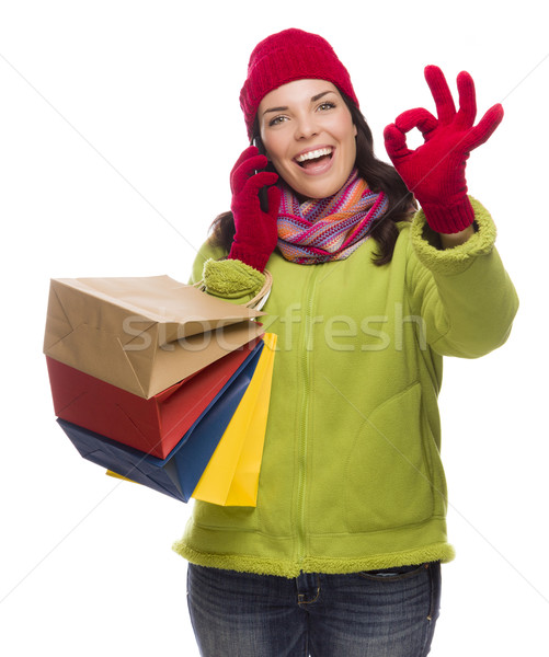 Stock photo: Mixed Race Woman Holding Shopping Bags On Phone Ok Gesture