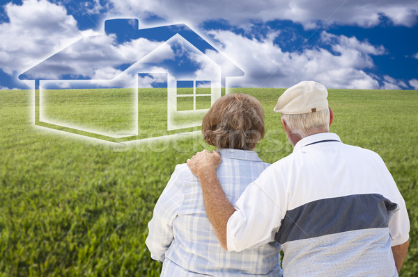 Stock photo: Senior Couple Standing in Grass Field Looking at Ghosted House