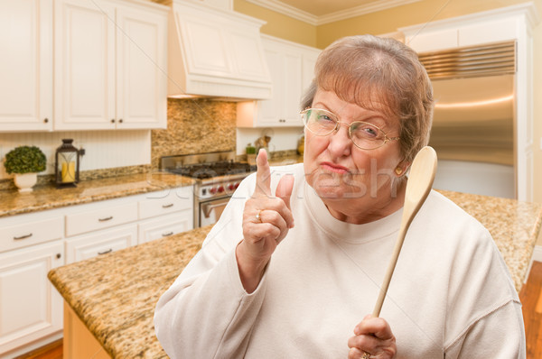 Senior Adult Woman Scolding with The Wooden Spoon Inside Kitchen Stock photo © feverpitch