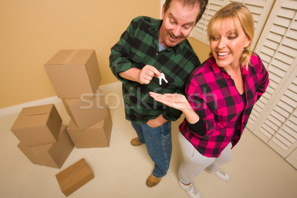 Goofy Excited Man Handing Keys to Smiling Wife Stock photo © feverpitch