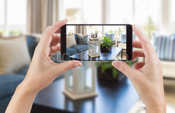 Stock photo: Female Hands Holding Smart Phone Displaying Photo of House Inter