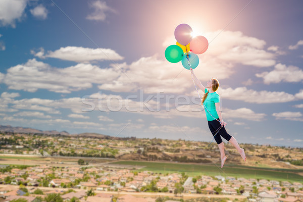 Young Girl Being Carried Up and Away By Balloons That She Is Hol Stock photo © feverpitch