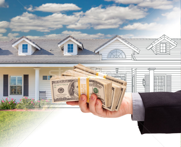 Hand Holding Stack of Money Over House Drawing Gradating Into Ph Stock photo © feverpitch