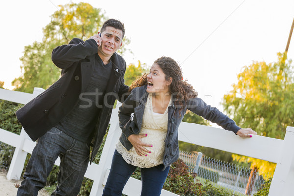 Pregnant Woman In Pain While Husband Uses Cell Phone Outside Stock photo © feverpitch