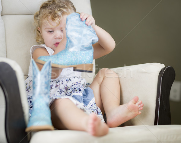 Blonde Haired Blue Eyed Little Girl Putting on Cowboy Boots Stock photo © feverpitch