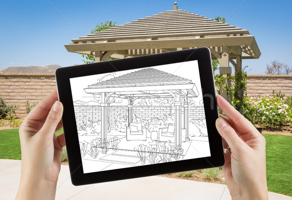 Female Hands Holding Computer Tablet with Drawing of Pergola on  Stock photo © feverpitch
