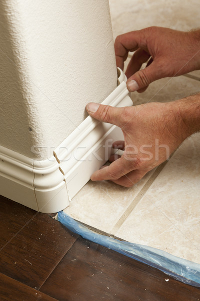 Stock photo: Contractor Installing New Baseboard with Bull Nose Corners and N
