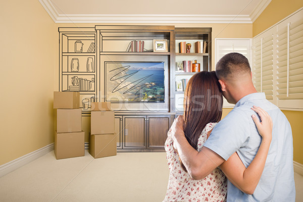Young Couple Looking At Drawing of Entertainment Unit In Room Stock photo © feverpitch