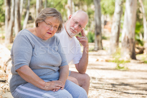 Upset Senior Woman Sits With Concerned Husband Outdoors Stock photo © feverpitch