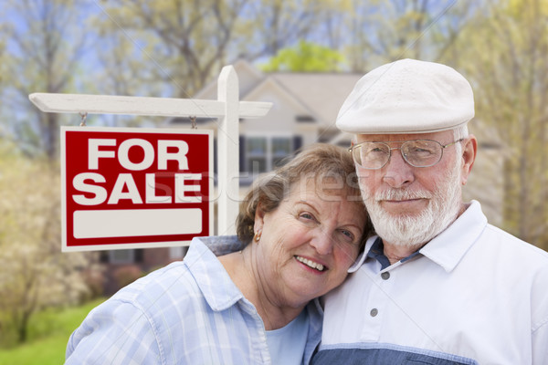 Happy Senior Couple Front of For Sale Sign and House Stock photo © feverpitch