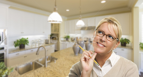 Daydreaming Woman with Pencil Inside Beautiful Kitchen Stock photo © feverpitch