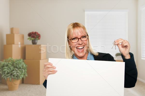 Woman with Blank Sign and House Key in Empty Room with Packed Mo Stock photo © feverpitch
