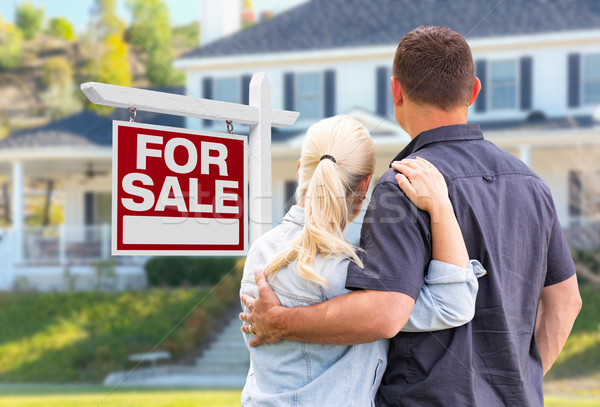 Young Adult Couple Facing Front of For Sale Real Estate Sign and Stock photo © feverpitch