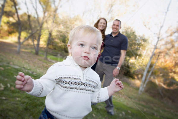 Cute Young Boy Walking as Parents Look On From Behind Stock photo © feverpitch