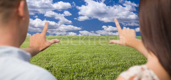 Couple Framing Hands Around Space in Grass Field Stock photo © feverpitch