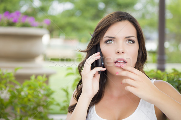 Stunned Young Adult Female Talking on Cell Phone Outdoors Stock photo © feverpitch